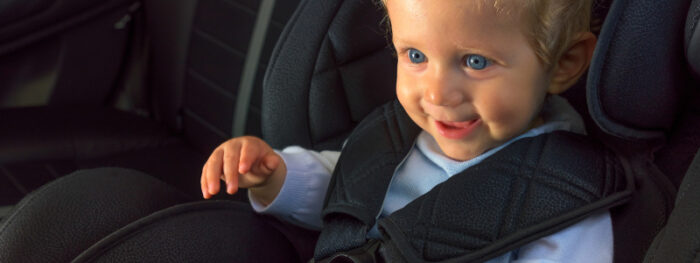 smiling toddler in the back of a car
