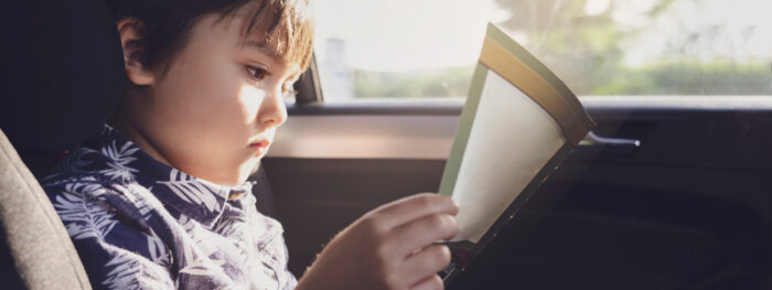 young boy looking at a sticker book in the car